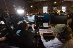 Two broadcast engineers sitting at video mixer