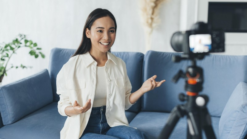 Happy woman sitting on sofa live streaming to camera